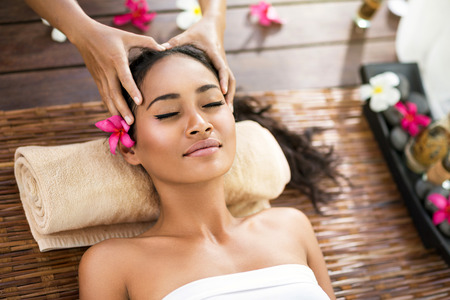 therapy: Portrait of young beautiful Balinese woman receiving head massage at spa