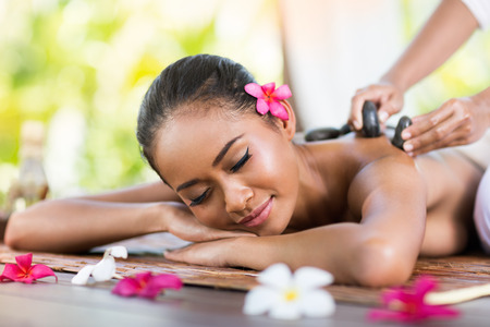 young woman receiving massage of back with stone massage Stock Photo