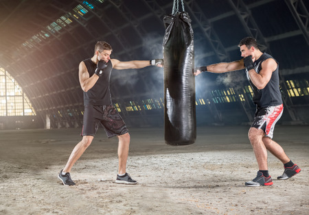 fighters: Two boxers hitting the sandbag