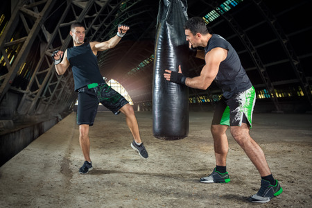 sandbag: boxer practicing with trainer