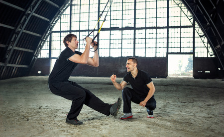 resistance: man exercising with a resistance band with trainer