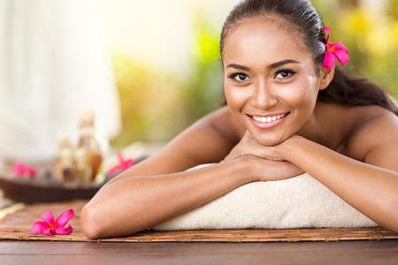 fresh face: Beautiful smiling girl outdoor portrait at massage spa. Serene happy Balinese woman relaxing looking joyful at camera Stock Photo