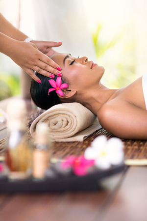 young woman receiving head massage in spa environment Stockfoto