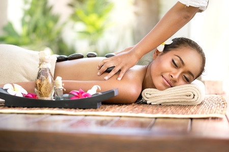 laying on back: Stone massage, beautiful woman getting spa hot stones massage in spa salon Stock Photo