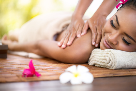 Beautiful young woman at spa outdoor, stone massage Stock Photo