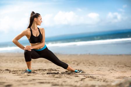 fitness: Attraente donna adatta che allunga sulla spiaggia, allenamento all'aperto