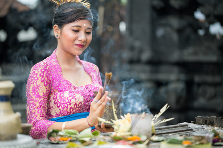 hindu temple: young Balinese woman to praying in Hindu temple