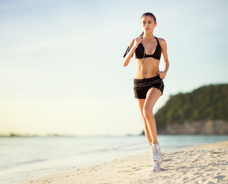 athletic: Young athlete female runs along the beach