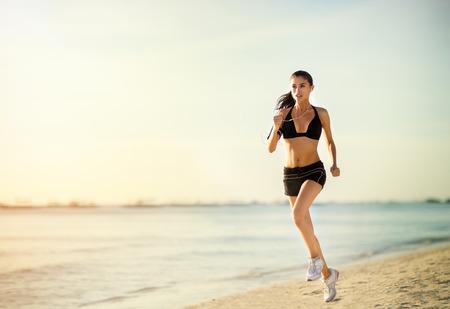 실행 여자 해변에서 실행. 여성 피트니스 일출  일몰 조깅 운동 웰빙 개념입니다. 스톡 콘텐츠
