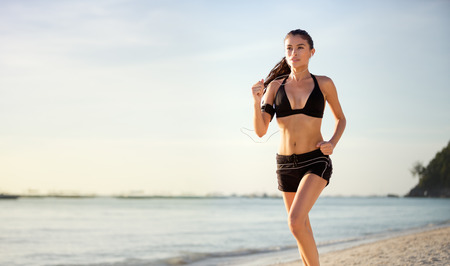 fit: Woman runner jogging on beach Stock Photo