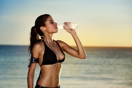 water activity: Fitness beautiful woman drinking water and sweating after exercising on summer hot day in beach. Female athlete after workout Stock Photo