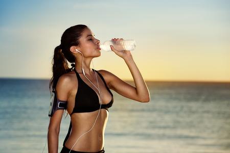 sudando: Fitness hermosa mujer de agua potable y sudando después de hacer ejercicio en el día de verano caliente en la playa. Atleta femenina después del entrenamiento