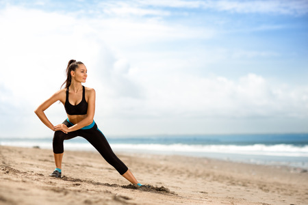 young beautiful sportswoman doing exercises on beach Stockfoto