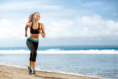 Jogging athlete woman running at sunny beach. Fitness runner girl training outside by the ocean sea in full body length in summer