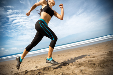 Female running on beach over beautiful sky Stock Photo