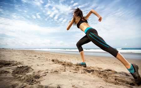 lifestyle woman: healthy lifestyle sports woman running on seaside Stock Photo
