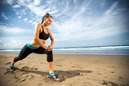 Aantrekkelijke vrouw die zich uitstrekt benen na het lopen op het strand Stockfoto