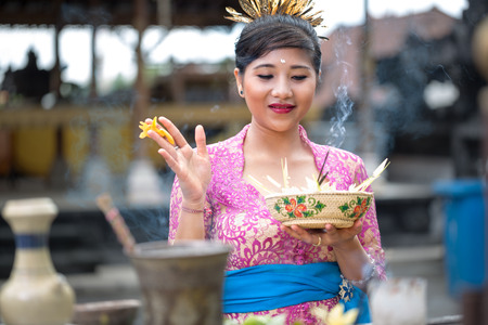 sacrificio: Mujer balinesa joven que ruega en templo hindú