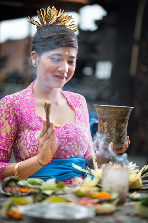 ceremonial clothing: Young Balinese woman praying in traditional ceremonial clothing