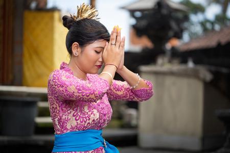 manos unidas: Chica balinesa rezando, ella de rodillas con las manos juntas en frente de su cabeza