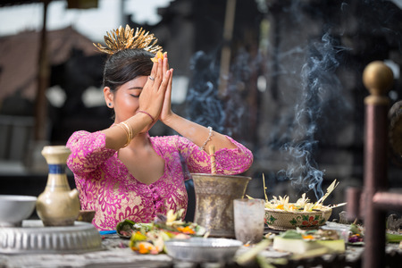 Beautiful Asian woman prays in the temple. Bali. Indonesia Imagens