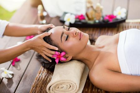 masaje facial: Masajista haciendo masaje de la cabeza de una mujer asi�tica en el sal�n del balneario