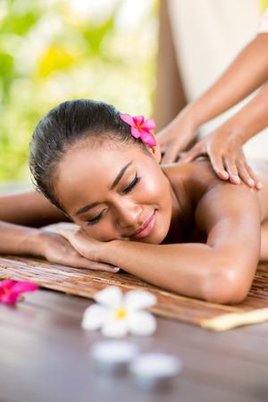 junge Frau mit Massage draußen im tropischen Garten