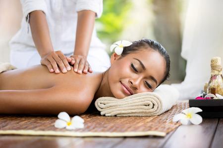 relaxamento: Spa massagem ao ar livre, mulher balinesa recebe a massagem traseira Imagens