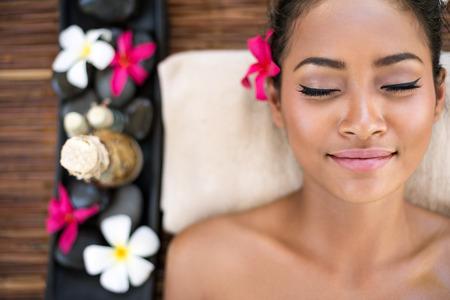 Serene beautiful spa woman relaxing on massage desk