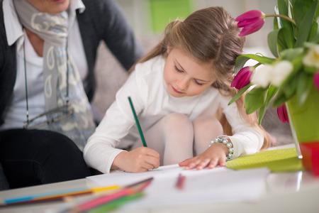 niños escribiendo: Escritura de la niña, mientras que su abuela mantuvo, jugando juntos