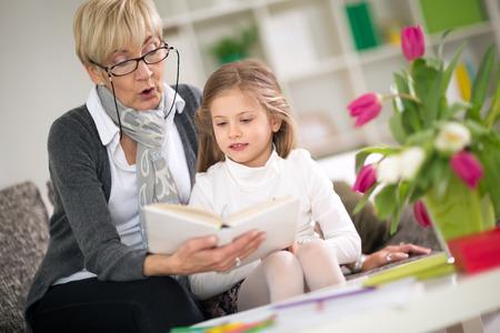 Grandmother reading interesting book her little granddaughter photo