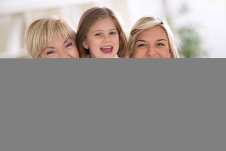 Happy women with little girl, grandmother and mother embracing little girl