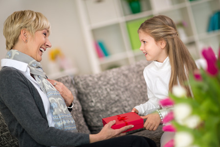 Granddaughter giving gift to her grandmother, surprise for sweetheart grandma