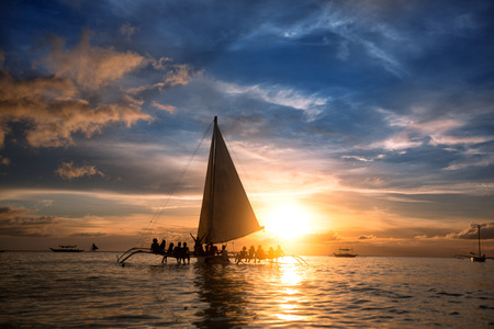 sailboats: Group of people sitting on sailboat at  ocean and looking  sunset
