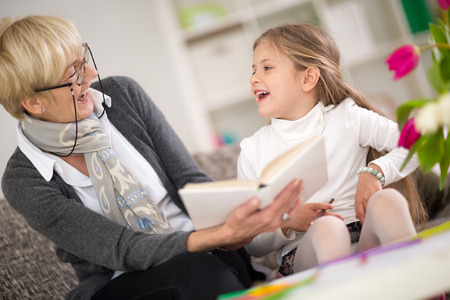 interested: little girl with grandma reading interested book