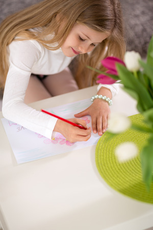 table scraps: Adorable girl making gift card for mother day, writing in living room Stock Photo