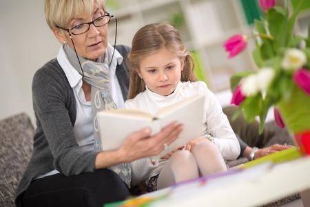 niños estudiando: miradas interesadas chica en el libro que su abuela leer