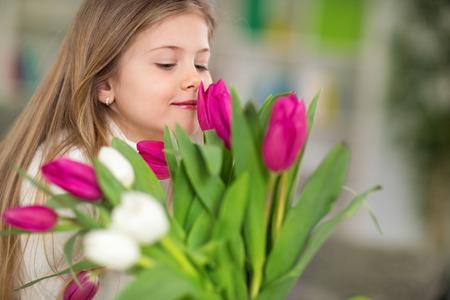 olfato: niña con el ramo de flores de primavera, disfrutar del olor de los tulipanes