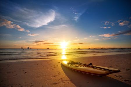 beach sunset: Surfboard on the beach at sunset