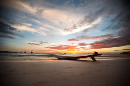 deserted: surfboard on a deserted beach at sunset Stock Photo