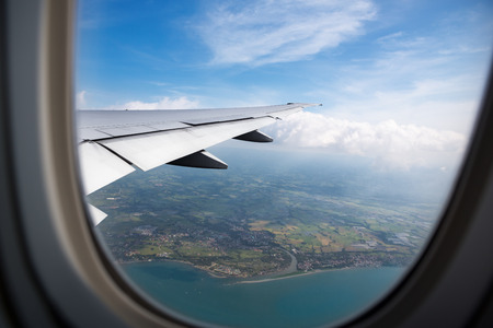 飛行機の窓から地球と海と飛行機の翼ビュー 写真素材