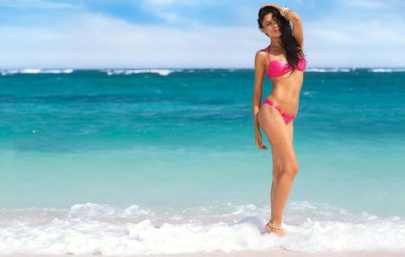 Seduction woman in pink bikini standing in the shallow water at the beach