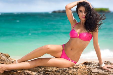 Sexy vrouw in roze bikini met zee op achtergrond