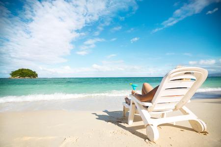 칵테일 해변에서 해변 의자에 누워 편안한 여름 휴가를 즐기는 여자