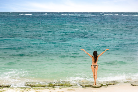 peaceful girl standing on the beach and looking at sea, concept freedom and peace Stock Photo