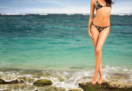 Cuerpo de mujer curtida en bikini en el fondo del mar