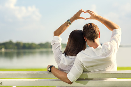 female and male hands making up heart shape over blue sky Stockfoto