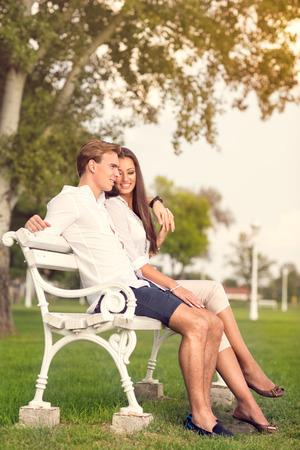 couple relaxing: young couple enjoying on bench in park