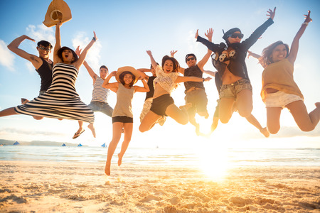People: jumping at the beach, summer, holidays, vacation, happy people concept Stock Photo