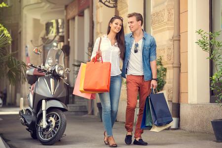 shopping: Par de jóvenes con bolsas de compras en la calle de la ciudad